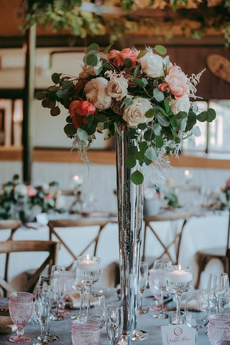 Tall arrangement on a silver mercury vase featuring coral charm peonies, white peonies, playa blanca roses, quicksand roses, light pink astilbe, silver plumosa and silver dollar eucalyptus.