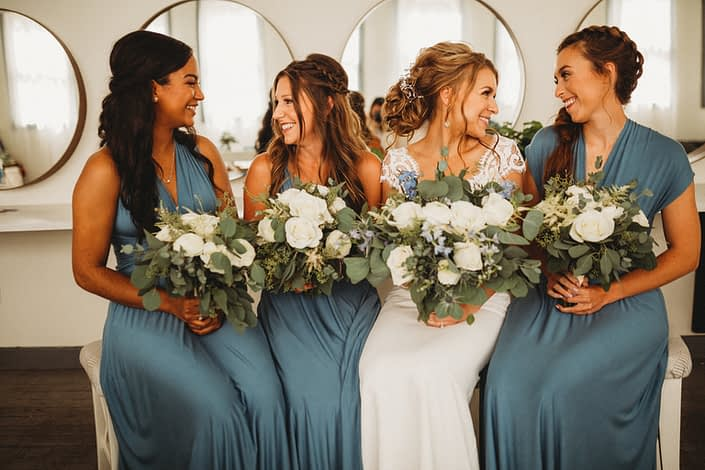 Bride and her bridesmaids holding white and dusty blue bouquets made of roses, ranunculus, astilbe, eryngium, delphinium, and eucalyptus.