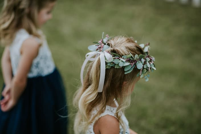 Flower girl wearing a tie-back flower crown made of eucalyptus and astilbe.