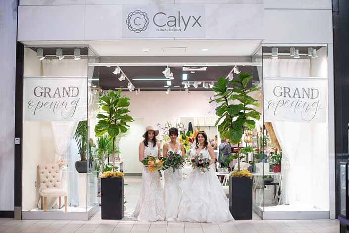 Calyx Floral Design boutique grand opening storefront photo with three brides holding bridal bouquets