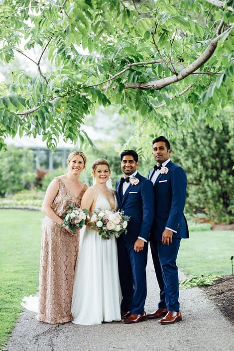 Jill and Jason's Romantic Blush Calgary Zoo Wedding bridal party; groom and groomsmen wearing navy suits and blush spray rose boutonnieres; bride and bridesmaid holding bouquets designed with white o'hara garden roses, quicksand roses, white ranunculus, and light pink astilbe with eucalyptus greenery.