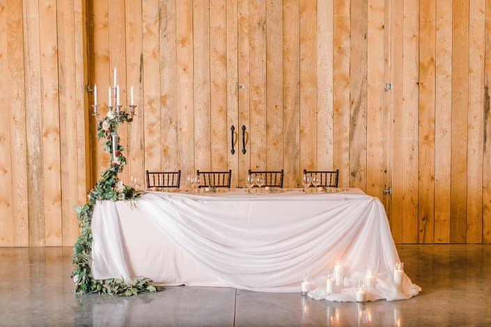 Blush and Burgundy winter wedding photoshoot at Sweet Haven Barn - head table decorated with candlestick and floral garland