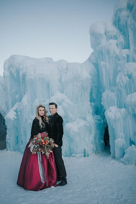 a styled engagement photoshoot at the edmonton alberta ice castles with the bride holding a bouquet of burgundy frittilaria, red helleborus and red tulips