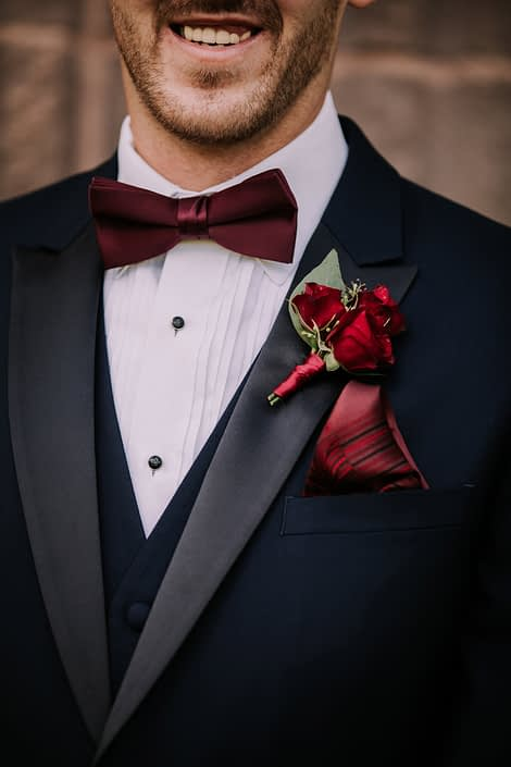 Groom boutonniere designed with a small cluster of burgundy spray roses accented by seeded eucalyptus and wrapped with burgundy satin.