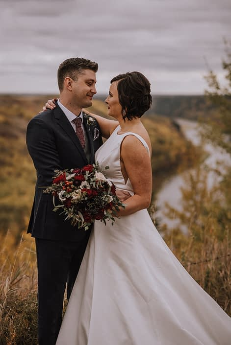 bride and groom at canyon ski resort overlooking the red deer river holding a burgundy and navy bridal bouquet