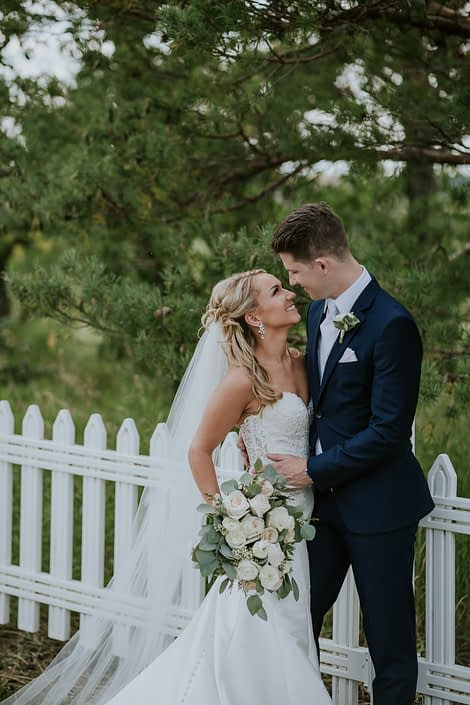 Rustic Chic Blush Wedding - Brooke and Levi looking at each other while holding a blush and ivory bouquet featuring white o'hara garden roses, quicksand roses, playa blanca roses, ranunculus, astilbe, wax flower and eucalyptus greenery.
