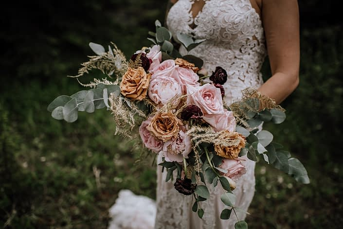 bride in white lace wedding dress holding a bridal bouquet of pink peony, pink ohara garden roses, plum ranunculus, toffee roses, gold plumosa, and cinerea eucalytpus