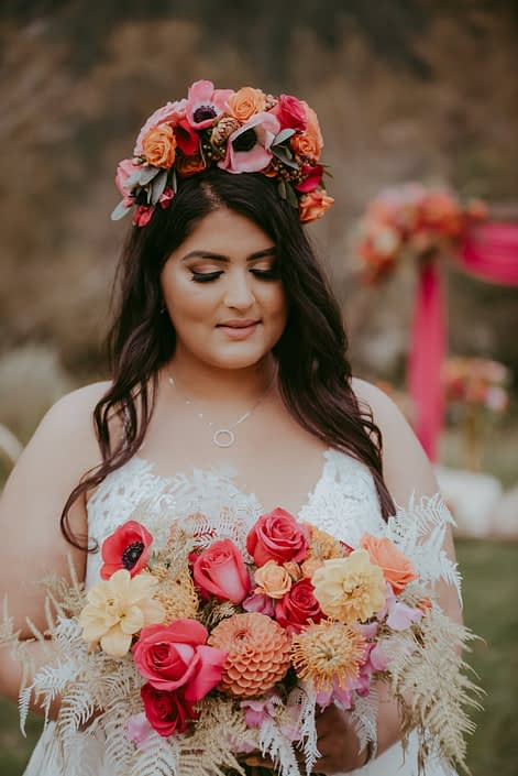 Bride with bold and colourful flower crown and bridal bouquet designed with anemones, zinnias, roses, dahlias, sweet peas, bleached bracken fern, gold plumosa and eucalyptus
