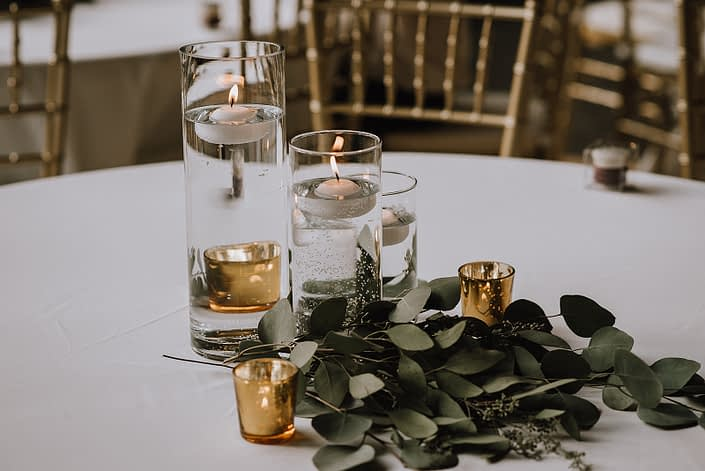 White linens on table with clear cylinder vases and candles and fresh eucalyptus at base