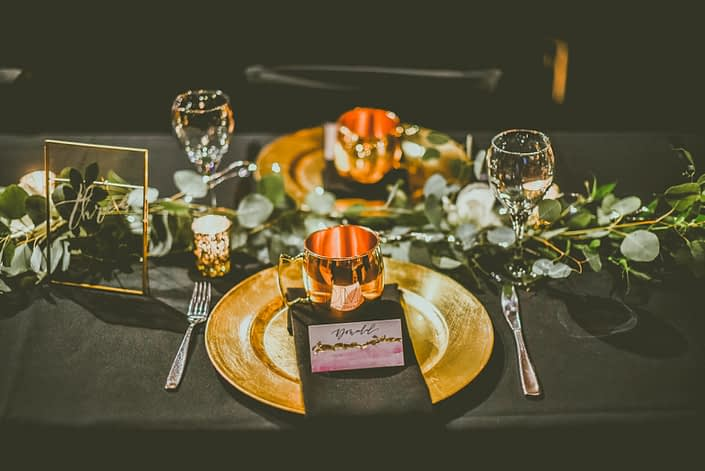 Black and gold decorated reception table with a fresh eucalyptus garland. Engraved moscow mule mugs were placed on each plate.