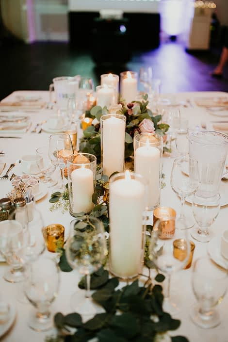 Fresh loose greenery such as silver dollar eucalyptus, seeded eucalyptus and italian ruscus at the base of white cylinder pillar candles.