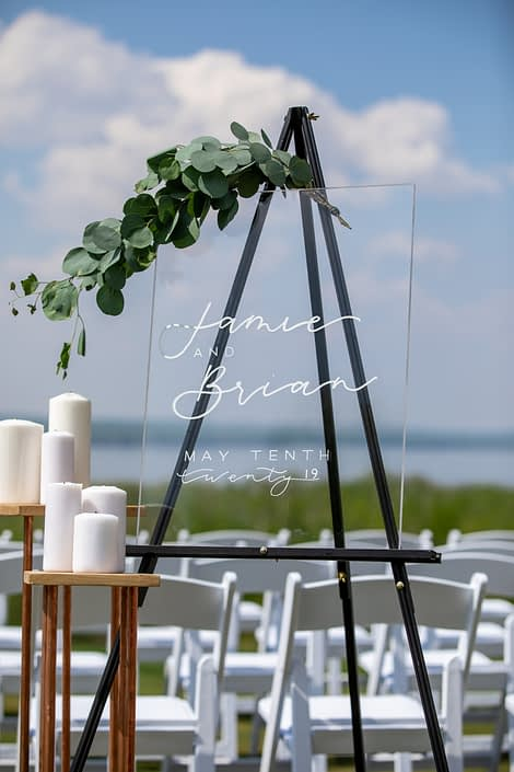 clear acrylic wedding welcome sign on black easel with white pillar candles and fresh eucalyptus greenery accent
