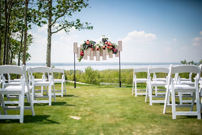 archway florals with black monstera coral peony and burgundy peony with geometric archway backdrop and white folding chairs overlooking sylvan lake