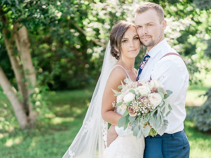 Taryn and Warren embracing; groom wearing rose gold boutonniere; bride holding dusty rose bouquet featuring rose gold painted scabiosa pods, white o'hara garden roses, quicksand and amnesia garden roses, ranunculus, astilbe, babies breath, dusty miller and eucalyptus.
