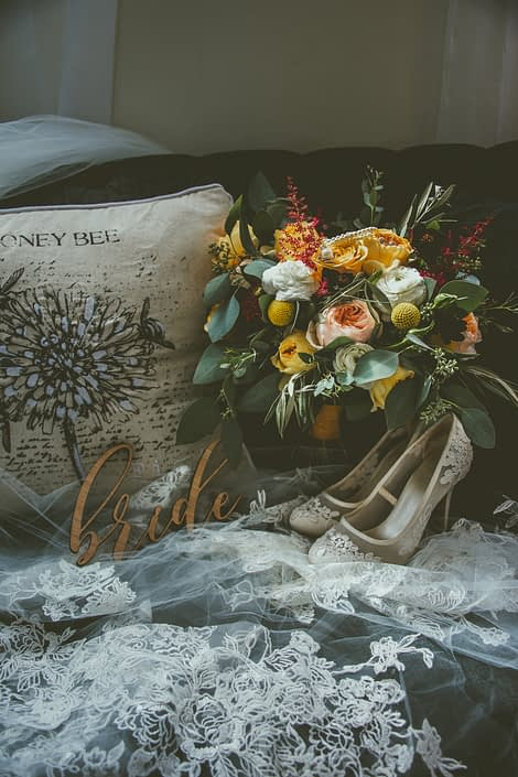 Bride's shoes, veil and mustard yellow bridal bouquet designed with juliet garden roses, caramel antike garden roses, white ranunuclus, golden mustard roses and accented by plum dahlias, craspedia, red astilbe, olive branches and a mixed variety of eucalyptus greenery.