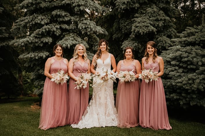 Bride with bridesmaids; rustic boho bouquets designed in white and blush tones including roses, ranunculus, phalenopsis orchids, olive branches, eucalyptus, bunny tail, bleached bracken fern and astilbe; dusty mauve bridesmaids dresses