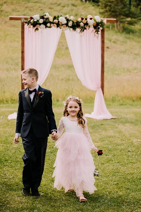 Ringbearer and flower girl - ringbearer wearing a burgundy boutonniere designed on a magnet; flower girl hoop made with black bacarra and white o'hara roses with a small amount of greenery.