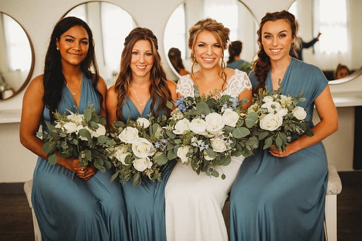 Bride, Kaitlin and her bridesmaids; bridal bouquet designed with Tibet roses, white ranunculus, white astilbe, blue delphinium, dusty blue eryngium, and eucalyptus greenery; bridesmaids bouquets made of similar white flowers.