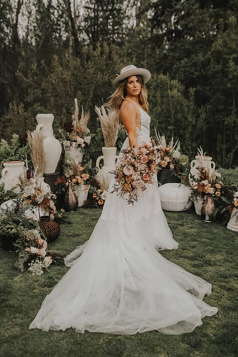 Modern Boho Bride with terracotta toned bouquet surrounded by boho decor and botanicals