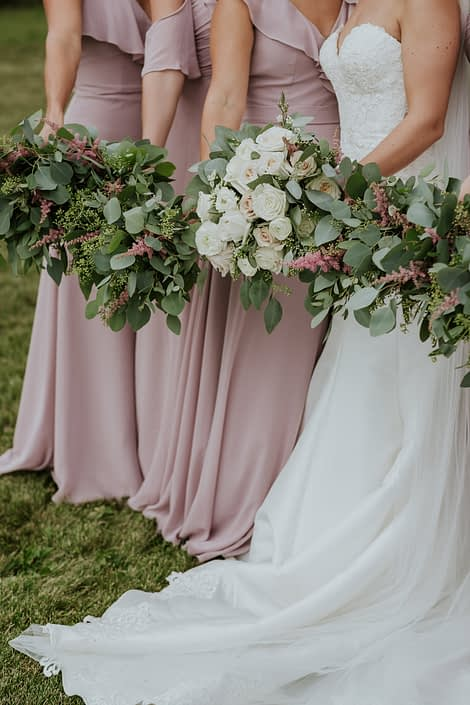 Blush bridesmaid dresses and white bridal gown with eucalyptus greenery and pink astilbe bridesmaid bouquets and a blush and ivory bridal bouquet designed with white o'hara garden roses, quicksand roses, playa blanca roses, ranunculus, wax flower, astilbe and eucalyptus greenery.