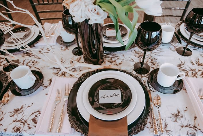 Place setting for Canyon Ski Resort Open House 2019 featuring black and ivory marie noir linen tablecloth, black and white plates, black goblets, and black vases filled with quicksand and toffee roses and white dream tulips; manzanita branches laying on table.
