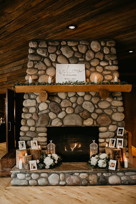 stone fireplace decorated with candles, photo frames, greenery and flower arrangements featuring white hydrangeas