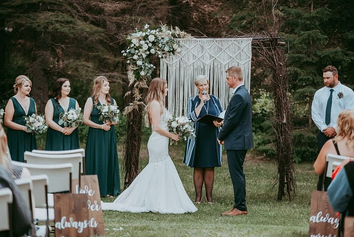Natural white and green wedding ceremony; bride and groom standing in front of natural wood archway decorated with macrame and white and green corner floral arrangement