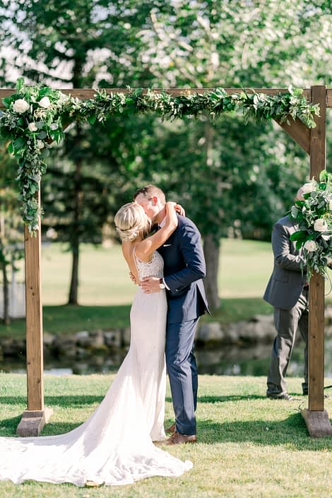 Kayla and Joel kissing under a wooden archway covered with arrangements and garlands made of salal, Italian ruscus, plumosa, eucalyptus and Tibet roses.