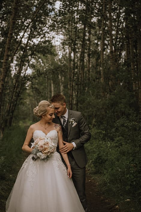 bride in strapless wedding dress with groom in grey suit holding a bridal bouquet of hydrangea, blush roses and dusty miller