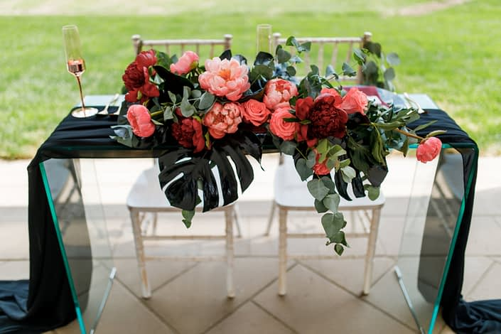 clear glass sweetheart head table with black voile runner and gold wedding glasses with floral arrangement designed with black monstera, burgundy and coral peony, coral amsterdam roses and cinerea eucalyptus