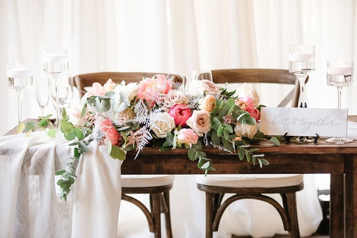 Sweetheart table arrangement designed with coral charm peonies, quicksand roses, playa blanca roses, peach ranunculus, light pink astilbe, silver plumosa, salal and a variety of eucalyptus greenery.