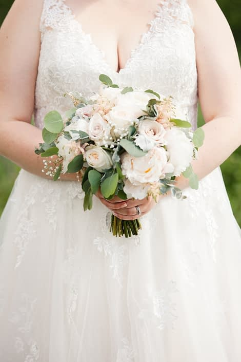 Bride wearing ivory lace bridal gown and holding cream and blush bouquet featuring white peonies, white o'hara garden roses, quicksand roses, babies breath, pale pink astilbe, dusty miller and a mixed variety of eucalyptus.