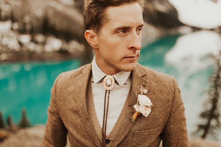 Moraine Lake Elopement Styled Shoot - male model wearing ivory boutonniere, brown jacket and bolo tie