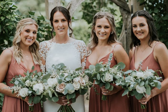 Rusty Rose Wedding; Bride and rusty rose bridesmaids with white, ivory and blush bouquets designed with roses and ranunculus