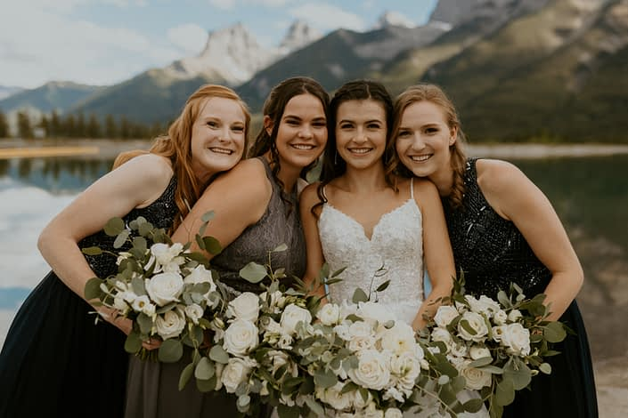 White rural elegance wedding - Bride and bridesmaids with white bouquets featuring lisianthus, ranunculus, roses, spray roses, sweet peas, eucalyptus and Italian Ruscus