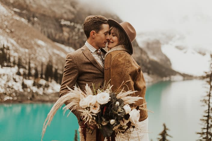 Moraine Lake Elopement Styled Shoot - couple embracing and girl wearing brown jacket and ivory bridal gown and hat holding pampas grass bouquet with blush roses and pops of red tied with trailing ribbons.