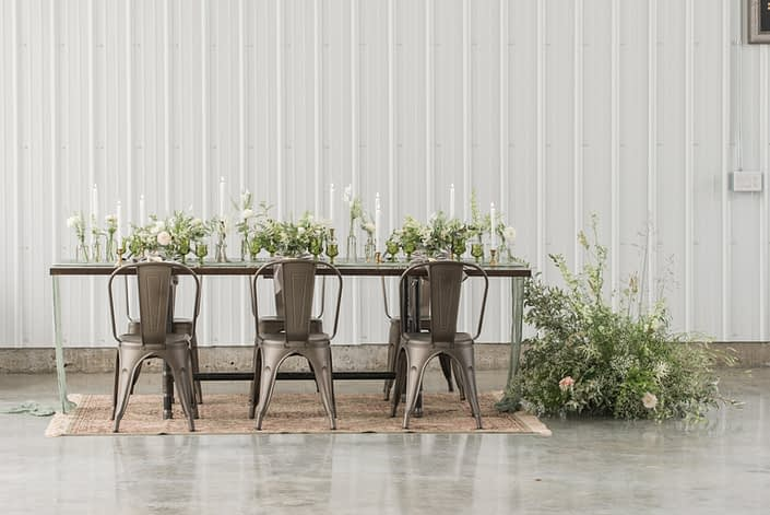 Modern, vintage, romantic industrial styled shoot table with industrial chairs, wild and natural floral arrangements designed with white flowers and lots of greenery atop a vintage persian rug.