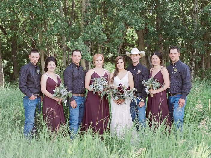 Country chic bridal party; bridesmaids in burgundy; cowboys; bride wearing lace and carrying a burgundy bouquet featuring quicksand roses and burgundy dahlias.