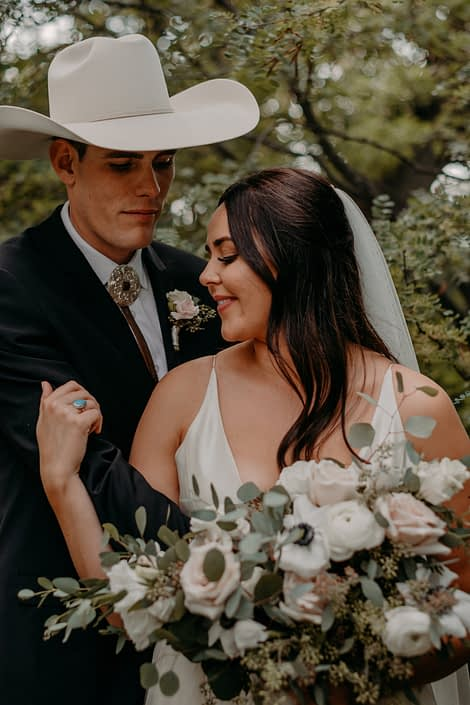 Erika and Colt's Blush and Mauve Country Wedding - bride and groom embracing; groom is wearing a cowboy hat and blush and ivory boutonniere made of spray roses; bride is holding a blush, ivory and white bridal bouquet featuring quicksand roses, lisianthus, panda anemones and ranunculus with fresh eucalyptus.