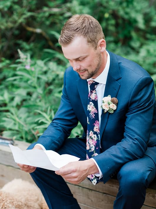 Groom reading message from the bride wearing a rustic yet elegant dusty rose boutonniere.
