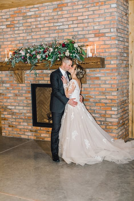 Bride and groom kissing in front of a fireplace with a blush and burgundy floral garland on the mantel
