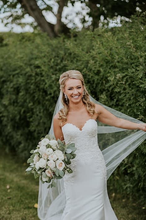 Brooke holding her veil and a blush and ivory bridal bouquet made of white o'hara garden roses, ranunculus, quicksand roses, playa blanca roses, astilbe, wax flower and eucalyptus greenery.