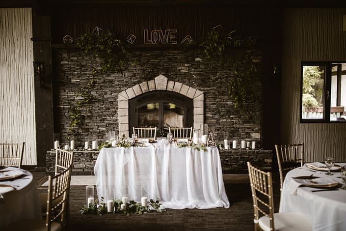 Canyon Ski Resort grand stone fireplace and sweetheart table decorated with ivory linens, white pillar candles, gold geometric accents, and fresh loose greenery.