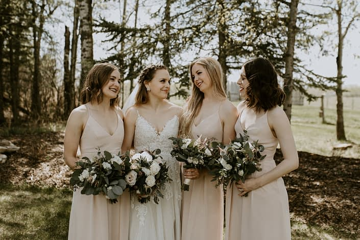 Bride and bridesmaids with bouquets designed with pink astilbe, burgundy astrantia, eryngium, white ranunculus, playa blanca roses and quicksand roses with eucalyptus greenery