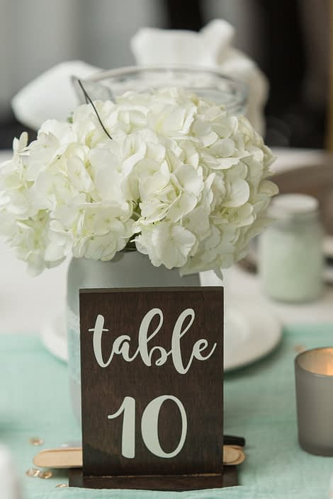Megan and Steven's Rustic Pastel Wedding centrepieces with wooden table number and mason jar centrepiece with white hydrangea.