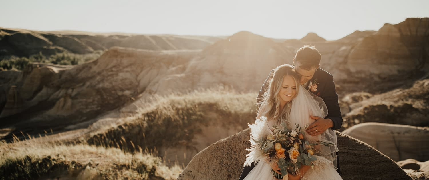 Bride and groom, Lizelle and Shayne, with peach and burgundy boho bridal bouquet
