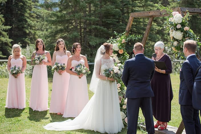 Bride and bridesmaids standing by the wooden hexagon archway at the wedding ceremony. They are all carrying bouquets made with white o'hara garden roses, quicksand roses, pale pink ranunculus, astilbe, eryngium, and a mixed variety of eucalyptus greenery.