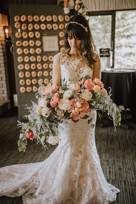 Bride wearing a lace gown from Novia Mia Bridal and holding a crescent shaped bouquet featuring coral charm peonies, peach ranunculus, quicksand roses, playa blanca roses, pale pink astilbe, silver painted plumosa and a mixed variety of eucalyptus greenery.