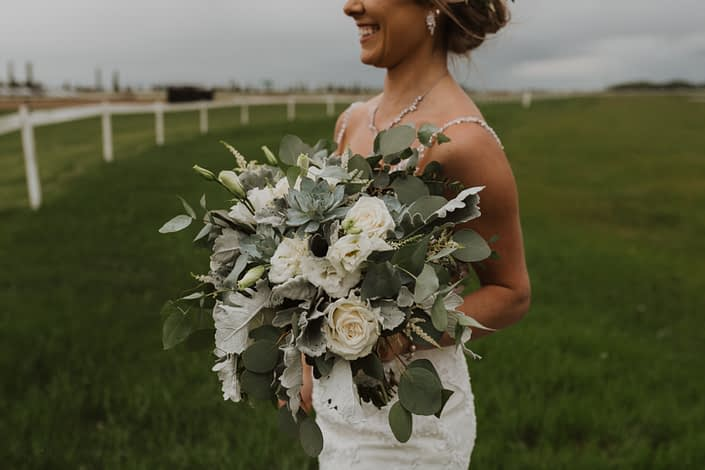 White and grey green bridal bouquet with a vintage feel designed with Playa Blanca roses, lisianthus, blue star succulents, astilbe, dusty miller, and a variety of eucalyptus greenery.