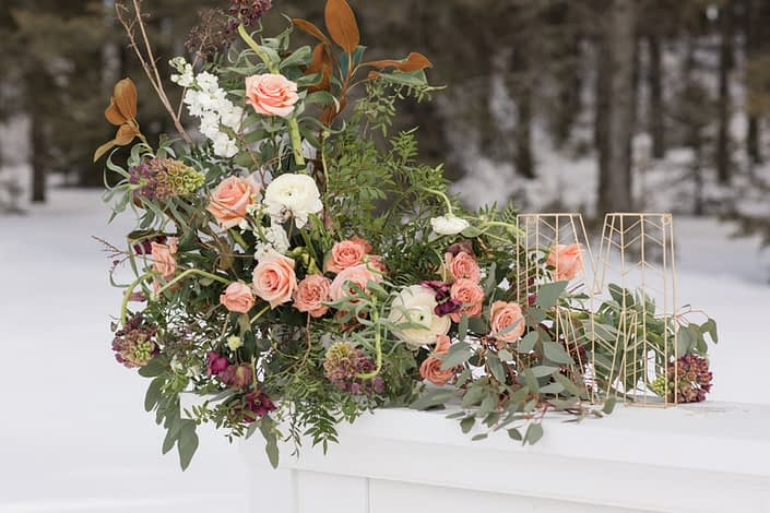 Gold Geometric letter M monogram on white mantle with flowers arrangement designed with peach roses, magnolia blush ranunculus and burgundy frittilaria